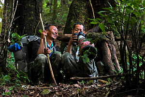 Two guides looking at photographs taken on camera whilst sitting on forest floor. Wuliangshan Nature Reserve, Jingdong, Yunnan Province, China. October 2017.  -  Magnus Lundgren / Wild Wonders of China