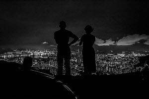 Silhouette of man and woman looking out over Hong Kong from Victoria Peak, Hong Kong Island, China. June, 2016. - Magnus Lundgren / Wild Wonders of China