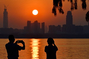 Two people taking a picture of the sunset skyline of Wuhan, East Lake Greenway park, Wuhan, Hubei, China. June 2018 - Staffan Widstrand / Wild Wonders of China