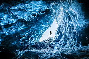 Man at mouth of an ice cave beneath Vatnajokull Glacier, Iceland. March 2018  -  Guy Edwardes