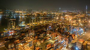 Timelapse from day to night looking over Tsing Yi container port, with cranes filling container ships, Hong Kong, China, 2017. - Jurgen Freund