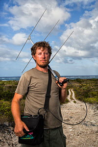 Portrait of scientist Nathan Cooper holding radio-telemetry equipment to track Kirtland's warbler (Setophaga kirtlandii). Cat Island, Bahamas. April 2017. - Karine Aigner
