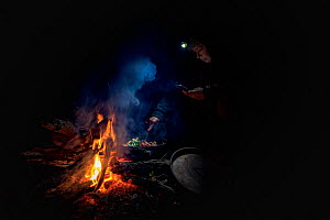 Researchers keeping warm by a fire next to the Mitta Mitta river, whilst monitoring gill nets which have been placed in the river to capture Platypus (Ornithornychus anatinus). Mitta Mitta River, Dart...  -  Doug Gimesy