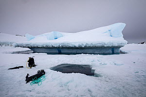 Diving equipment beside hole cut in sea ice by divers. Iceberg in background. Tasiilaq, East Greenland. April 2018.  -  Franco  Banfi