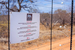 A sign on a fence of a game reserve bordering South Africa's Kruger National Park warns poachers that the horns of the reserve's rhinos have been treated and are unfit for human consumption. September...  -  Neil Aldridge