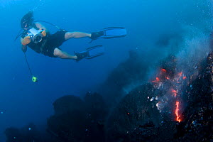 Videographer filming pillow lava erupting underwater at Kilauea Volcano, Hawaii. - Doug Perrine