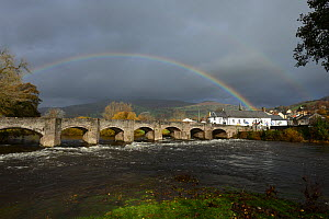 A rainbow over Crickhowell Bridge rebuilt in 1706, Grade 1 listed, the River Usk in spate and Table Mountain in the background, Brecon Beacon National Park, Breconshire, Wales, UK. November 2018. - Will Watson