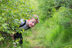 Boy hiding during forest kindergarten session. Aberdeen, Aberdeenshire, Scotland, UK. Editorial use only - SCOTLAND: The Big Picture