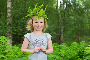 Girl wearing leaf crown during forest kindergarten session, standing amongst ferns. Aberdeen, Aberdeenshire, Scotland, UK. Editorial use only  -  SCOTLAND: The Big Picture