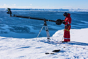 Cameraman Lindsay McCrae using a jib arm filming from ice shelf for BBC Dynasties Penguin programme, Atka Bay, Antarctica. March 2017. - Stefan Christmann