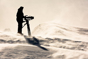 Cameraman Lindsay McCrae on sea ice filming frozen landscape and icebergfor BBC Dynasties Penguin programme. Atka Bay, Antarctica. October 2017. - Stefan Christmann