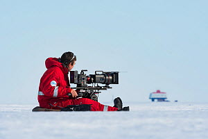 Camerman Lindsay McCrae filming towards Neumayer-Station III, Alfred-Wegener-Institut research station for BBC Dynasties Penguin programme Atka Bay, Antarctica. February 2017. - Stefan Christmann