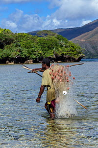 Kanak fisherman carrying his fishing net at the mouth of the Yate River, South Lagoon, Lagoons of New Caledonia: Reef Diversity and Associated Ecosystems UNESCO World Heritage Site. New Caledonia. - Duncan Murrell