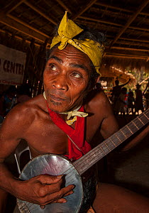 Man of the Batak indigenous tribe playing a stringed instrument in the Batak Visitors Centre at Barangay Concepcion, Puerto Princesa, Palawan, the Philippines. - Duncan Murrell