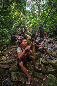 Young Batak man holding a home-made hunting rifle on an almaciga tree (Agathis philippinensis) cone collecting expedition in Cleopatra's Needle Critical Habitat, Palawan, the Philippines. Septembe...  -  Duncan Murrell