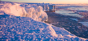 Ice shelf with sea ice forming in bay below, at sunrise. Atka Bay, Antarctica. March 2017.  -  Stefan Christmann