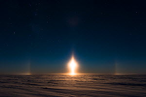 Moon bow, a halo around the moon during polar night. Sastrugi on sea ice in foreground. Atka Bay, Antarctica. June.  -  Stefan Christmann