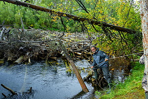 Man holding onto rope on the shore of the Lena River, nearly blocked with logs, Baikalo-Lensky Reserve, Siberia, Russia. August 2018. - Olga Kamenskaya
