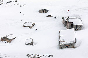 Group of snowshoe hikers passing snow covered mountain refuges in spring. These refuges are used in summer by herders to sleep while watching for their cattle, Gran Paradiso National Park, Aosta Valle... - David  Pattyn