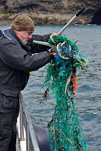 'Ghost Gear', abandoned fishing net and frayed plastic ropes, found floating in the sea and being hooked out of the water by a member of the Cornwall Seal Group Research Trust to lessen the ri...  -  Nick Upton