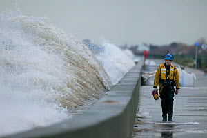 Waves crashing against the sea wall with a coast guard walking along it, Rhyl, Wales. January.  -  David  Woodfall