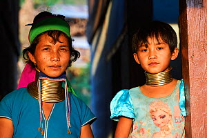 Portrait of a Kayan Lahwi woman with brass neck coil and traditional clothing. The young girl, her daughter, wears also the traditionnal neck coils but smaller and adapted to her age (8 years old). Sh...  -  Eric Baccega