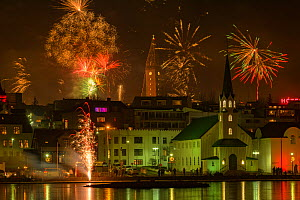 New Years Eve fireworks celebration in Reykjavik, Iceland with lights reflected in the water  -  Terry  Whittaker