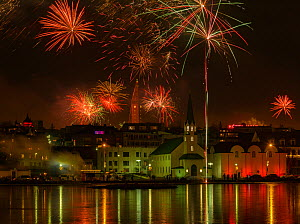 New Years Eve fireworks celebration in Reykjavik, Iceland, with lights reflected in the water  -  Terry  Whittaker