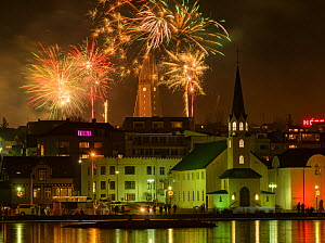 RF - New Years Eve fireworks celebration in Reykjavik, Iceland, with lights reflected in the water (This image may be licensed either as rights managed or royalty free.)  -  Terry  Whittaker