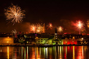 RF - New Years Eve fireworks celebration in Reykjavik, Iceland with lights reflected in the water (This image may be licensed either as rights managed or royalty free.)  -  Terry  Whittaker