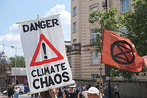 'Danger climate chaos' placard and Extinction Rebellion flag. Climate change protest march, Bristol, England, UK. 16 July 2019.  -  Ben Gillett