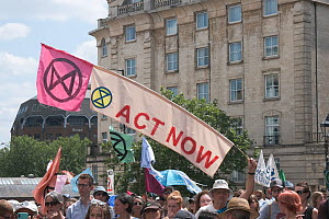'Act now' banner and Extinction Rebellion flag held aloft during climate change protest march. Bristol, England, UK. 16 July 2019.  -  Ben Gillett
