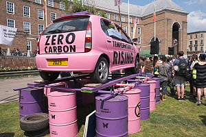 Pink car emblazoned with 'Zero carbon' and 'Temperature's rising', on top of oil drums. Extinction Rebellion climate change rally. Bristol, England, UK. 16 July 2019.  -  Ben Gillett