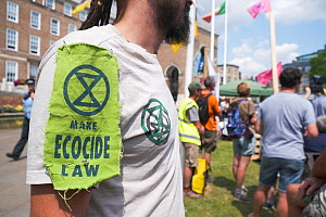Extinction Rebellion protester wearing logo and 'Make Ecocide Law' message. Climate change rally, Bristol, England, UK. 16 July 2019.  -  Ben Gillett