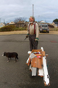 Kevin Whales picking up litter with home made cart whilst taking dog for a walk. Jaywick, Essex, England, UK, December.  -  David  Woodfall