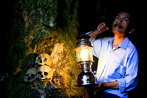 Man with lantern lighting up skulls on rock at Toraja cemetery. The Toraja culture of West and South Sulawesi revolves around death with funeral ceremonies an important part of daily life. Indonesia....  -  Enrique Lopez-Tapia