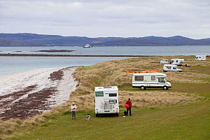 Couple with dog with numerous camper vans on East Beach, threat to nesting Little terns (Sterna albifrons). Ferry to Harris in the background, North Uist, Scotland, UK, June.  -  David  Woodfall