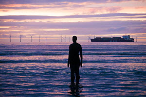 Silhouette of Sir Antony Gormley's 'Another Place' on Crosby beach, with shipping container in distance. Liverpool bay, Mersey Estuary, England, UK, October 2011.  -  David  Woodfall