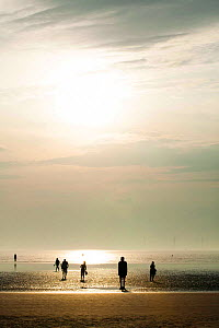 Silhouettes of Sir Antony Gormley's sculptures 'Another Place' on Crosby beach, with tourists in Liverpool bay. Mersey Estuary, England, UK, October 2011. - David  Woodfall