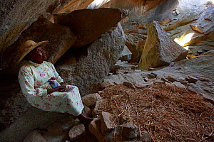 Woman sitting in cave in Anja Community Reserve. During colonial repression the local people hid in these caves, this lady was born on this 'nest' of rice hay surrounded by stones. Granite mou... - Cyril Ruoso