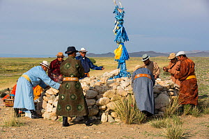 Men participating in ceremony around sacrificial altar / ovoo to worship mountain, milk libation poured as offerings to mountain deities. Great Gobi B Strictly Protected Area, Mongolia. 2018. - Cyril Ruoso