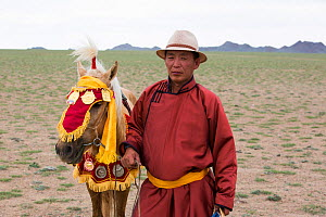 Horse trainer standing with race winning horse. Naadam festival, Great Gobi B Strictly Protected Area, Mongolia. August 2018. - Cyril Ruoso