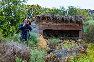 Man with camera on tripod beside bird hide. Faia Brava Reserve. Archaeological Park of the Coa Valley, Western Iberia, Portugal. April 2016. - Juan  Carlos Munoz