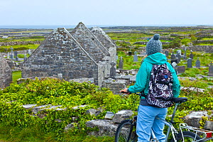 Cyclist looking at view of Seven Churches and countryside beyond. Inishmore, Aran Islands, County Galway, Ireland. May 2011. - Juan  Carlos Munoz
