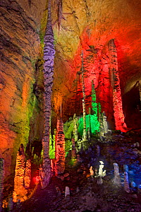 Stalagmites lit by coloured lights in Huanglong / Yellow Dragon Cave. Hunan Province, China. 2010.  -  Heather Angel