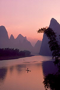 Man using pole to propel bamboo raft on Lijang / Li River, Karst peaks beyond. At dawn, Lijiang River Scenic Zone, Yangshuo county, Guangxi, China. - Heather Angel