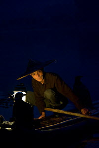 Li River fisherman in bamboo hat on raft with cormorants trained to bring back fish. In early morning, Yangshuo, Guangxi, China. 2009. - Heather Angel