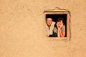 Photographers Steve and Ann Toon, looking through window in Tankwa Karoo National Park, South Africa  -  Ann  & Steve Toon