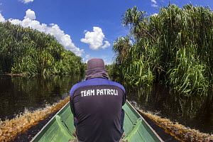 Traveling by 'klatok' with local field staff of the Borneo Nature Foundation on the Sabangau River bordering the Sabangau (peat-swamp) Forest in Central Kalimantan, Indonesia.  -  Duncan Murrell