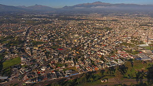 Aerial panning shot looking over Sangolqui, a suburb of Quito, with many volcanoes visible in background, including snowcapped Cotopaxi, Ecuador, 2018.  -  Morley Read